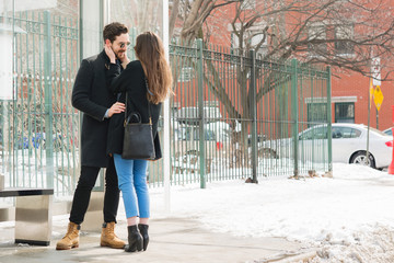 Couple Standing On Sidewalk In City During Winter