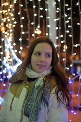 girl in a white coat in winter and glowing christmas garland