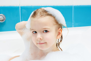 Little girl is taking a bath. Portrait of a cute baby with foam on her head.