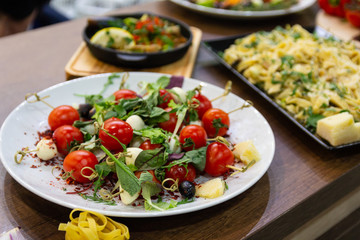 Tomato with greens on a plate served with spaghetti. Food