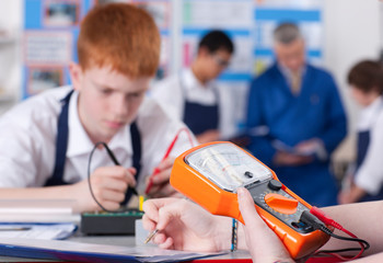 High school students using volt meter in electronics class