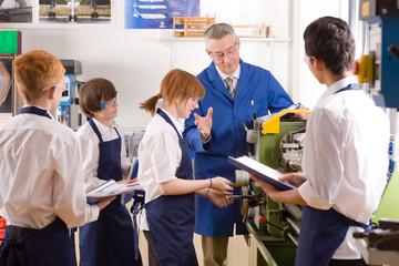 Teacher demonstrating lathe to high school pupils in metalwork class