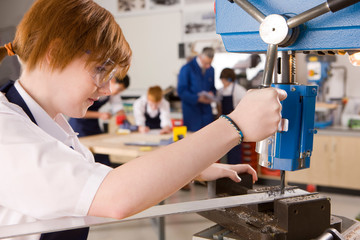 Female high school student using drill in metalwork class