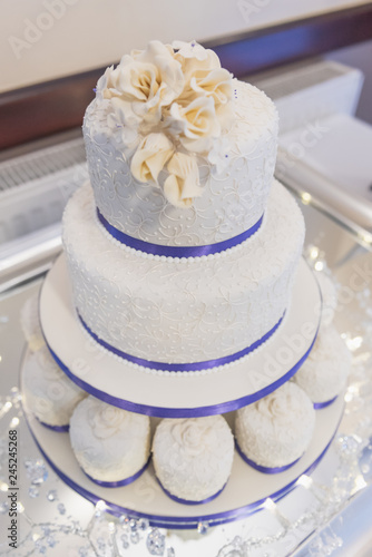 Wedding Cake With Ice And Blue Ribbon Decoration And White Roses On