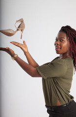Lovely black woman catching a high heel shoe