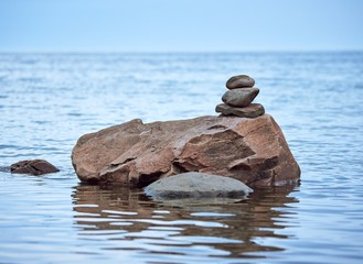 Stones stacked on top of a big rock on the sea water. Reposaari, Pori, Finland.  Concept of balance and harmony.