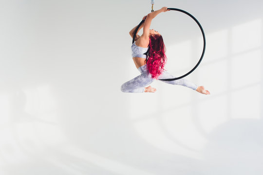 young redhead woman performs acrobatic elements in the air ring on a white background.