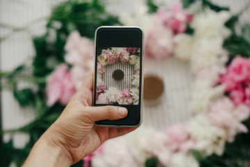 Hand holding phone and taking photo of peonies and coffee cup flat lay on rustic table cloth. Space for text. Coffee in glass in peony frame top view on table. Happy mothers day.