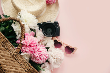 Stylish  flat lay with pink peonies in straw bag, hat, photo camera, retro sunglasses on pastel pink paper with copy space. International Women's Day. Hello spring. Summer vacation