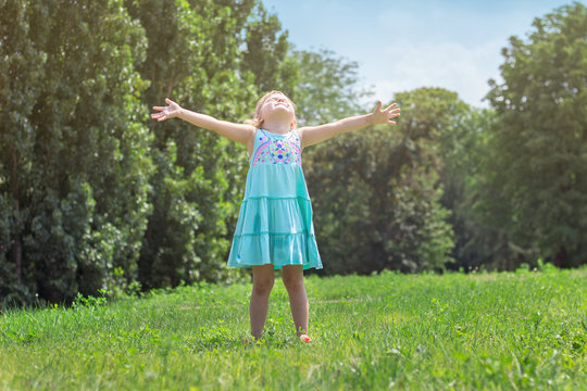 Little girl with her arms wide open, in the park; life and nature