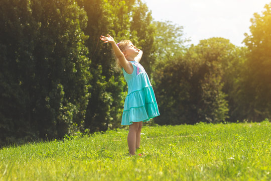 Little girl in the park with her arms open; life concept