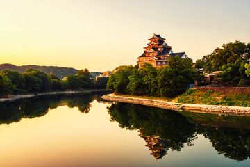 Castle in Okayama, Japan in the morning with river and colorful yellow sky at sunrise