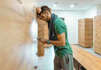 Tired athletic man using mobile phone while standing in locker room and taking a break from exercising