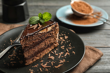 Plate with slice of chocolate cake and fork on table