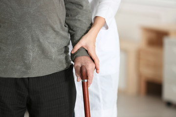 Elderly man with walking cane and female caregiver on blurred background, closeup view. Space for text