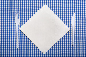 Plastic cutlery and napkin with space for text on plaid fabric, flat lay. Table setting