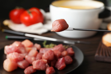 Raw meat fondue piece on fork over table, closeup. Space for text