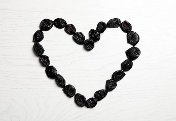Heart shaped frame of sweet dried plums on wooden background, top view with space for text. Healthy fruit