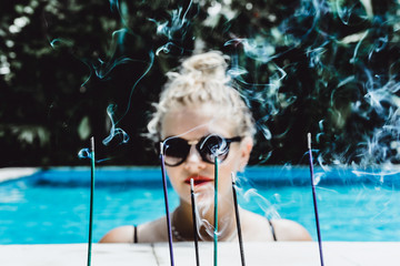 Blurred background of aromatic sticks and smoke with young beautiful blonde woman in sunglasses with a good figure with red lips make-up posing in a pool of blue water. Outdoor portrait close up.