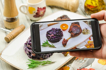 Young man taking photo of roasted duck leg dish on smartphone. Taking food photo with mobile phone.