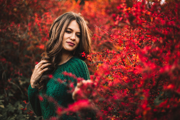 Beautiful woman posing on red tree leaf background.