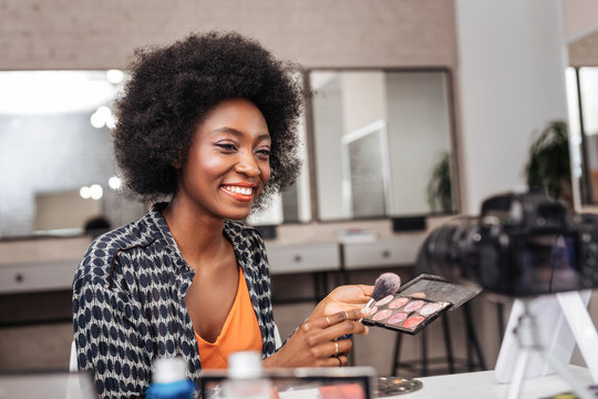 Cute dark-skinned woman with coral lipstick conducting online tutorial