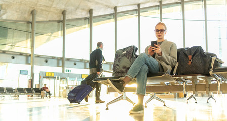 Fashionable blond young woman using her cell phone while waiting to board a plane at the departure gates at the airport terminal.