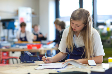 Female high school student writing notes at workbench in workshop