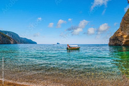 A small boat heads towards a rocky cove at Chomi Beach, also