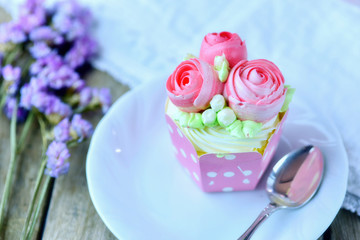 Vanilla cup cake and spoon on a plate with cup cake in background and flower  as decoration for valentine mother's day or birthday.