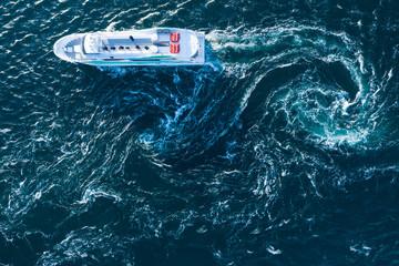 荒く渦巻く海と真直ぐに進む船