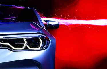 Wall Mural - Detail on one of the LED headlights modern car on red background