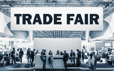 Fototapete - Crowd of people at a trade show booth with a banner and the text Trade Fair.