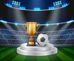 trophy and soccer ball on the podium with a football stadium background .