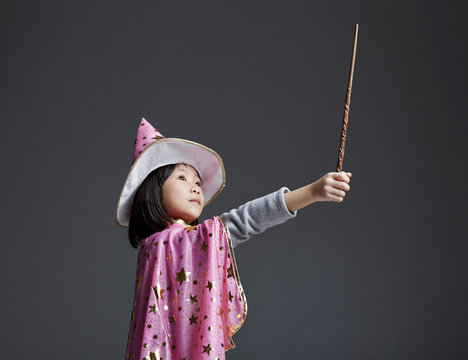 Asian little girl playing magic in the studio