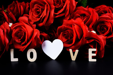 """Heart shape, Wooden letters word """"LOVE"""" and red rose on black background"""