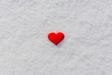 Red heart on glittering snow. Vilentine's day theme. Copy space