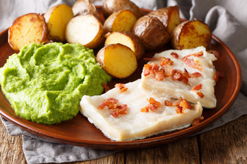 Cod Lutefisk with pea puree, baked potatoes and bacon close-up on a plate on the table. horizontal