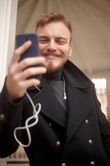 low angle shot of one young smiling man, 20-29 years old, texting and using his smart-phone.
