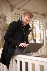 one happy young man, 20-29 years old, sitting on fence outdoors in park, while using his laptop (autonomously without power source) and typing on keyboard, with in-ear earbuds.