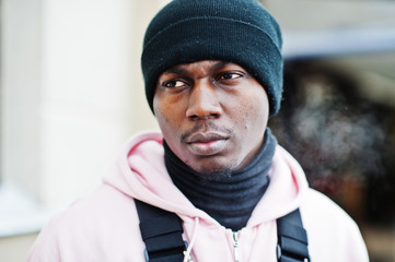 Close up head of stylish urban style african american man in pink hoodie and black hat posed. Frozen breath.