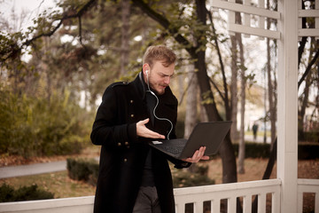 one young man, questing or doubting, while he is holding laptop in one hand outside in public park, communicating over Internet, video call or chat, could be with family or business related.