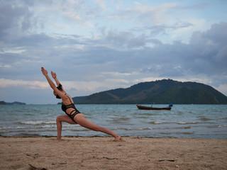 Caucasian woman practicing yoga at seashore wearing black swimsuit and medical anti-smog mask. Future concept