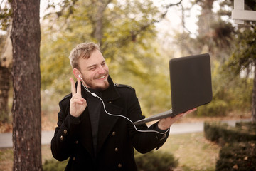 one young man, smiling and happy, holding laptop in one hand outside in park, communicating over Internet, video chat, could be with family of friend, gesturing with hand (two fingers as peace sign)