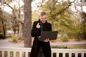 one young man, smiling and happy, holding laptop in one hand outside in park, communicating over Internet, video chat, could be with family of friend, gesturing with hand (Korean heart )