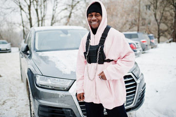 Stylish urban style african american man in pink hoodie posed against suv car at winter. Afro rapper guy.