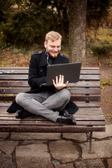 one young relaxed and smiling man, sitting casually on bench with crossed legs in public park, using laptop holding it with one hand. Formal wear or smart casual. Full length shot.