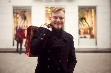 one young man, 20-29 years, looking to camera in front, upper body shot. Smiling holding shopping bag on his back,  with store front windows behind (in background blurry, out of focus)