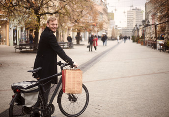 one young man, 20-29 years, standing in, pedestrian only, street holding his bicycle, and smiling to camera, with shopping bag. Pedestrians on street out of focus.