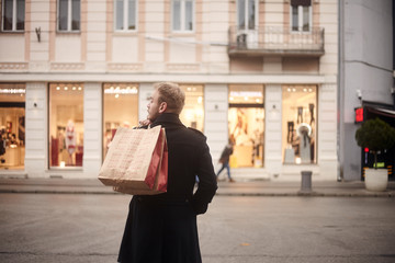 one young mans back, rear view, 20-29 years old, handsome and stylish, standing on a pedestrian street in city, looking, while holding two shopping bags on his back. Store front windows in distance.